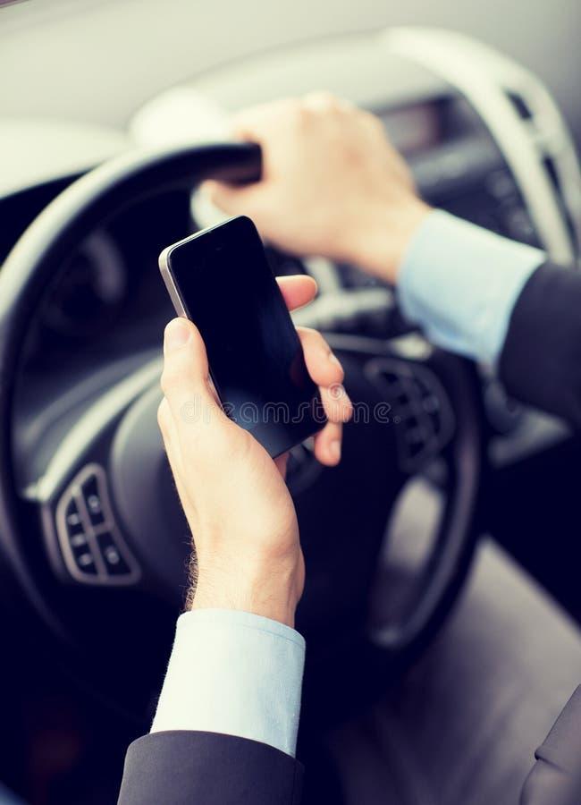 Hombre que usa el teléfono mientras que conduce el coche imagenes de archivo