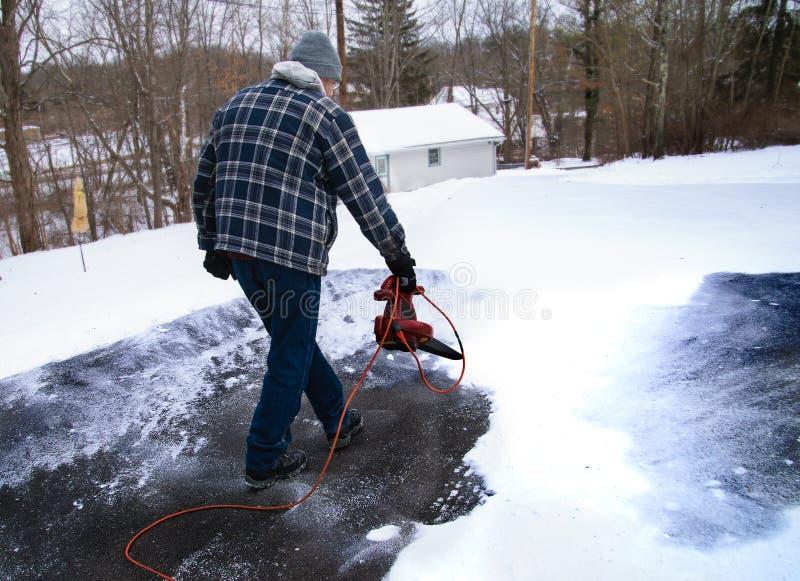 Hombre que usa el ventilador de hoja para despejar nieve de la calzada foto de archivo