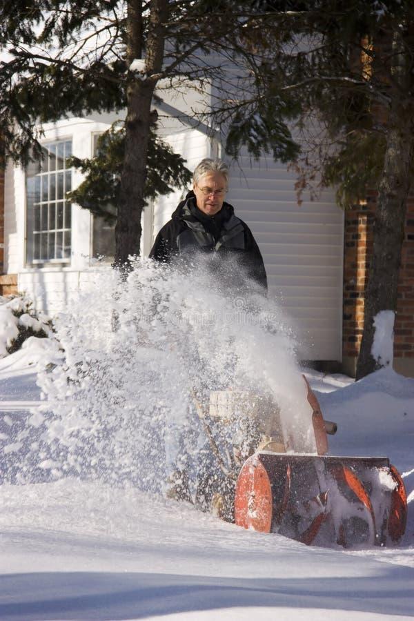 Hombre que usa el ventilador de nieve imagen de archivo