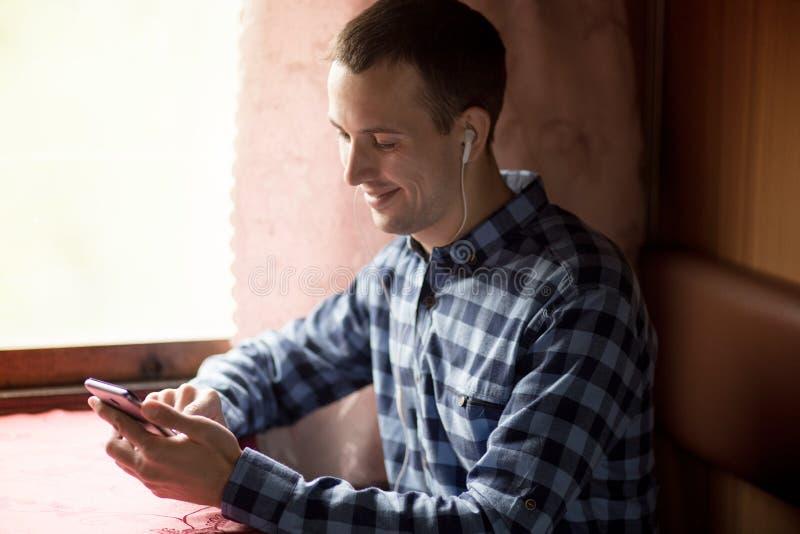Hombre que usa la aplicaci?n m?vil en su smartphone en la estaci?n de tren, viaje de negocios imagen de archivo libre de regalías