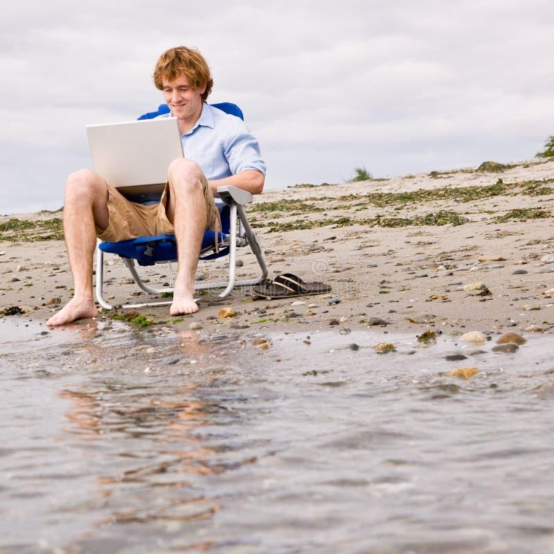 Hombre que usa la computadora portátil en la playa fotos de archivo
