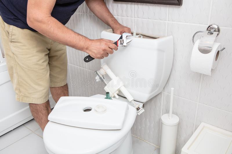 Hombre que usa la llave que repara la cisterna del retrete fotos de archivo