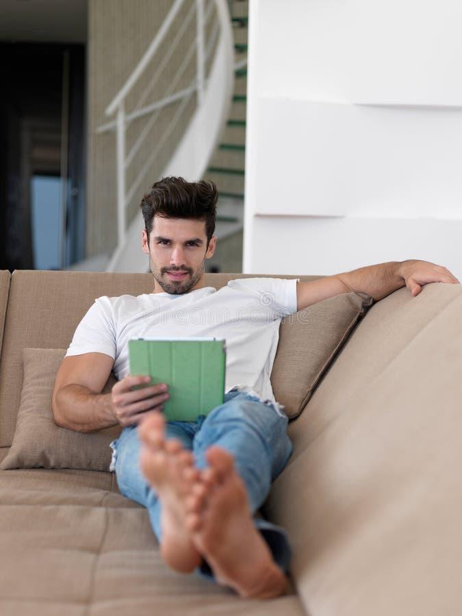 Hombre que usa la tableta del hogar foto de archivo
