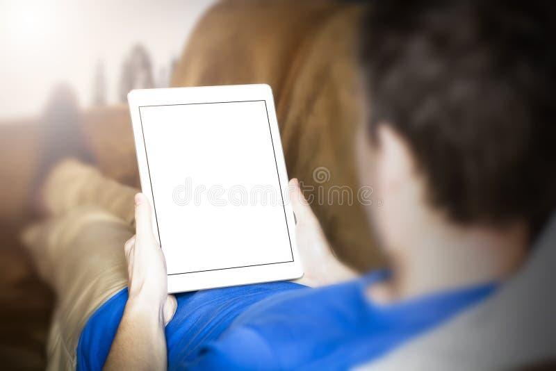 Hombre que usa la tableta mientras que miente en el sofá fotos de archivo libres de regalías