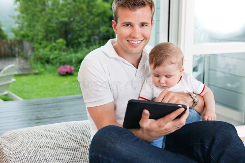 Hombre que usa la tablilla digital con el niño foto de archivo