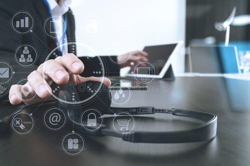 Hombre que usa las auriculares de VOIP con la tableta y el ordenador portátil digitales a fotos de archivo libres de regalías
