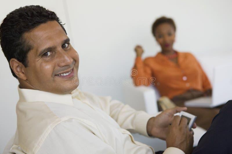 Hombre que usa PDA, mujer en fondo fotos de archivo