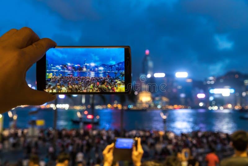 Hombre que usa su teléfono móvil para tomar la foto del cantado en la orilla del mar fotos de archivo libres de regalías