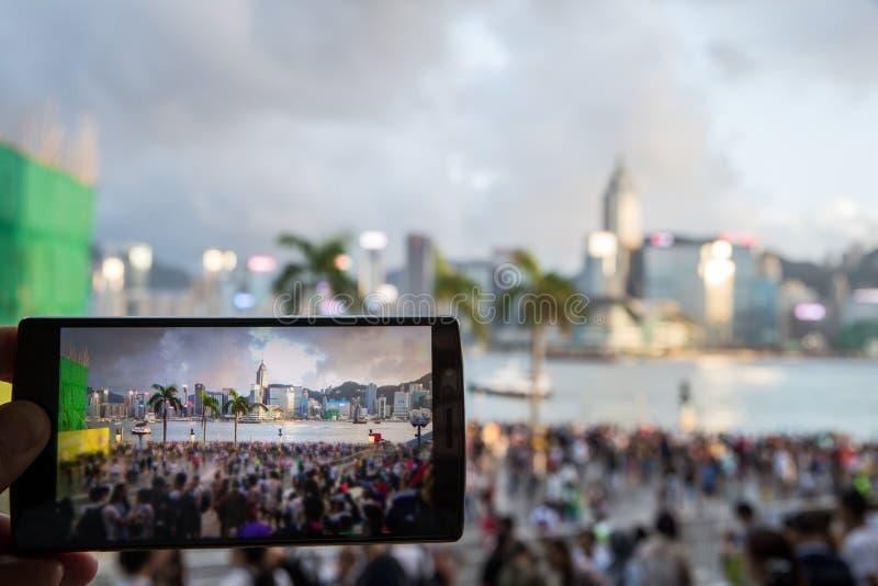 Hombre que usa su teléfono móvil para tomar la foto del cantado en la orilla del mar imagen de archivo libre de regalías