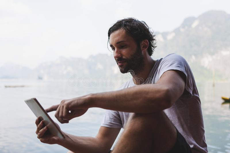 Hombre que usa su teléfono por un lago foto de archivo