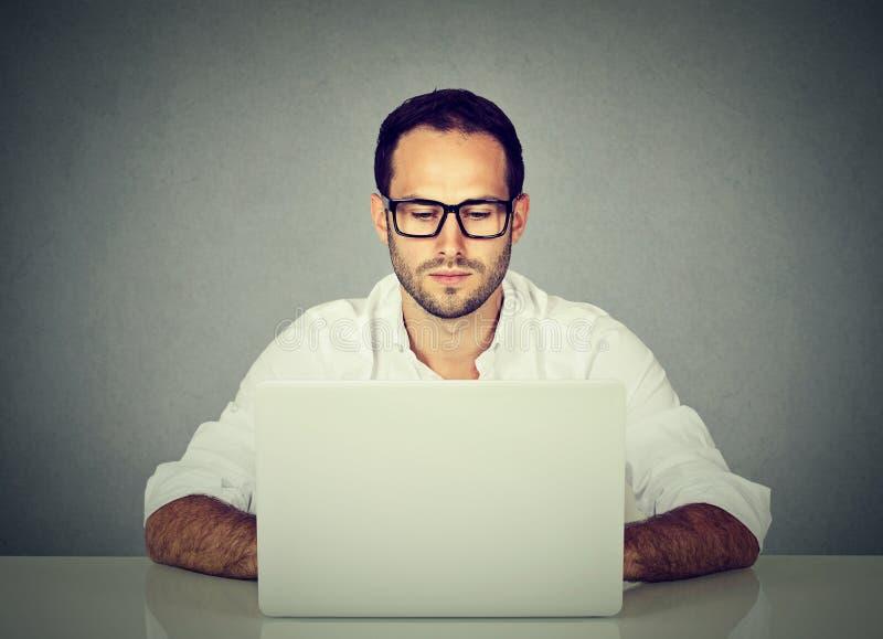 Hombre que usa un ordenador portátil fotografía de archivo
