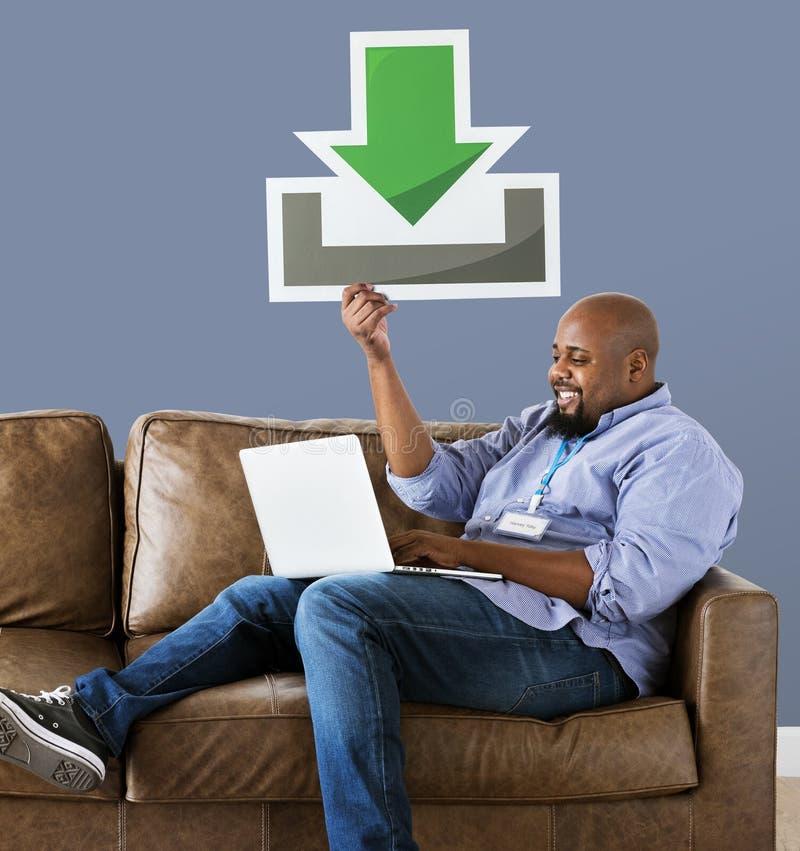 Hombre que usa un ordenador portátil y llevando a cabo un icono de la transferencia directa fotografía de archivo libre de regalías