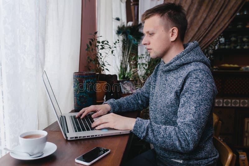 Hombre que usa un ordenador portátil y un teléfono móvil en un café Hombre joven que bebe c imagen de archivo