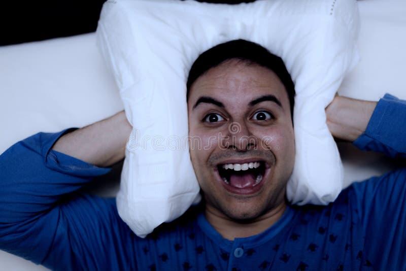 Hombre que usa una almohada para cubrir sus oídos imagen de archivo libre de regalías