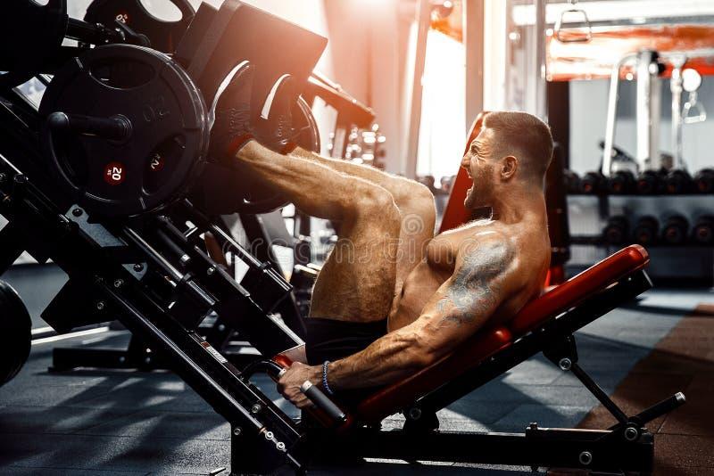 Hombre que usa una máquina de la prensa en un club de fitness Hombre fuerte que hace un ejercicio en sus pies en el simulador fotos de archivo libres de regalías
