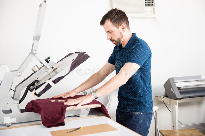 Hombre que usa una prensa del serigraph fotos de archivo libres de regalías
