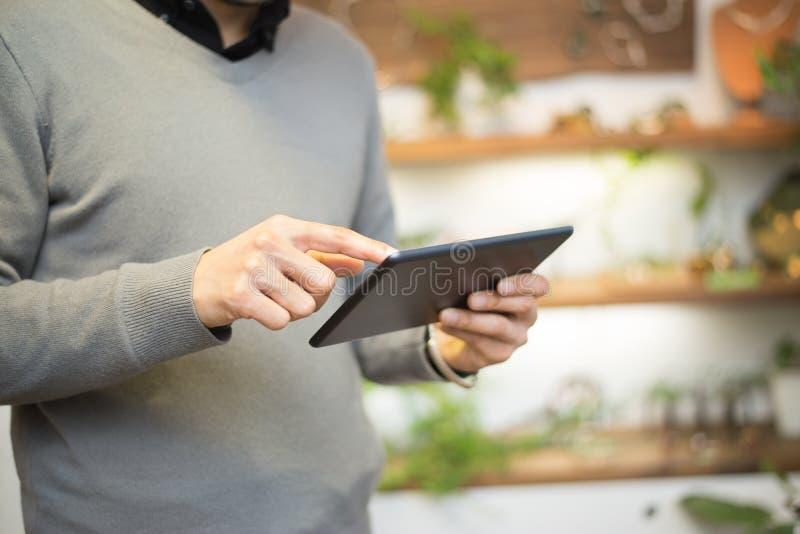 Hombre que usa una tableta digital en tienda imagen de archivo libre de regalías