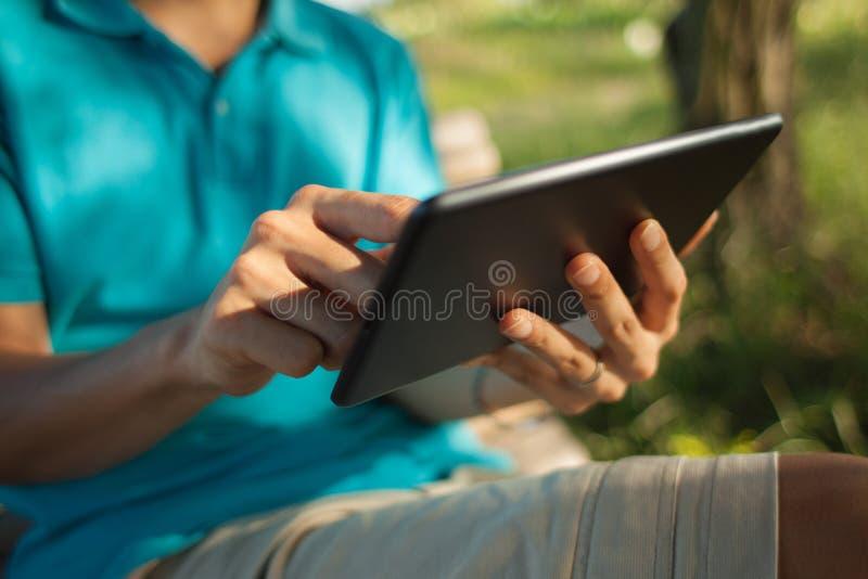 Hombre que usa una tableta digital en un parque imagen de archivo