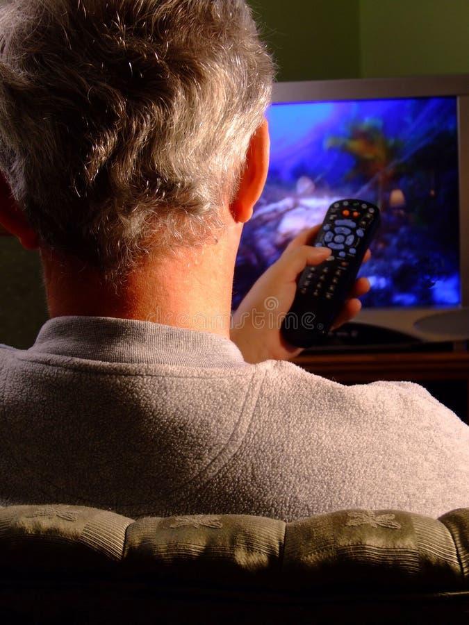 Hombre que ve la TV con el telecontrol fotos de archivo