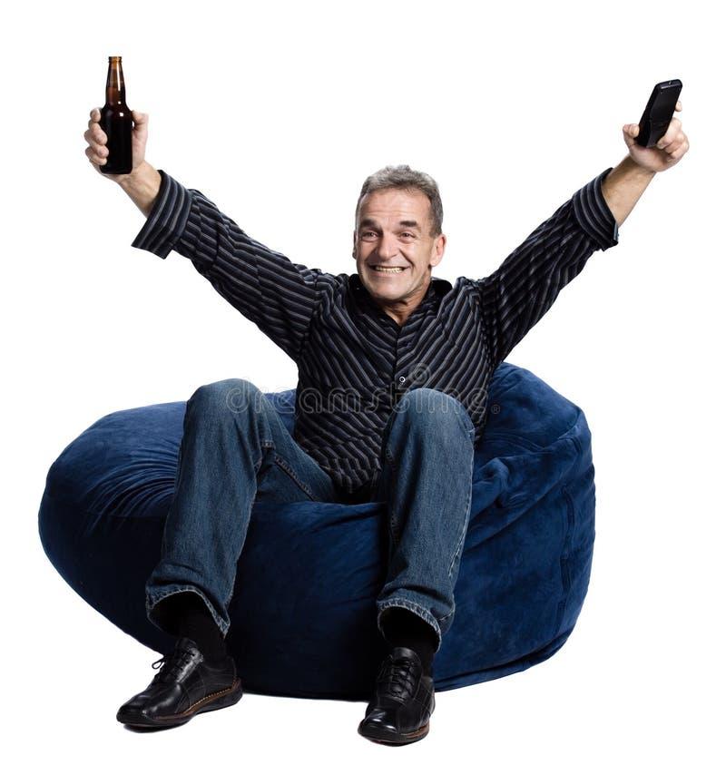 Hombre que ve la TV con una cerveza imagen de archivo