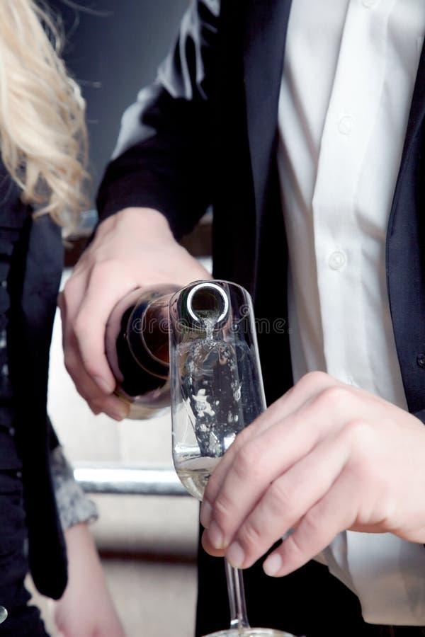 Hombre que vierte una flauta del champán imagen de archivo