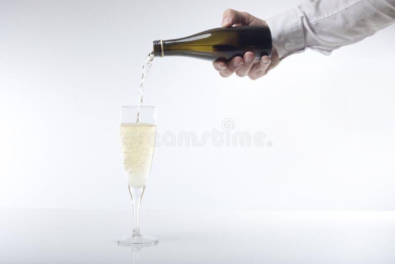 Hombre que vierte una flauta del champán fotografía de archivo