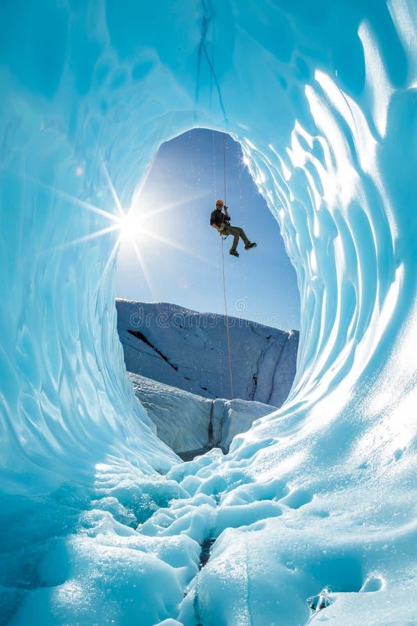 Hombre rappelling en la entrada de la cueva de hielo del glaciar en las montañas de Alaska fotografía de archivo