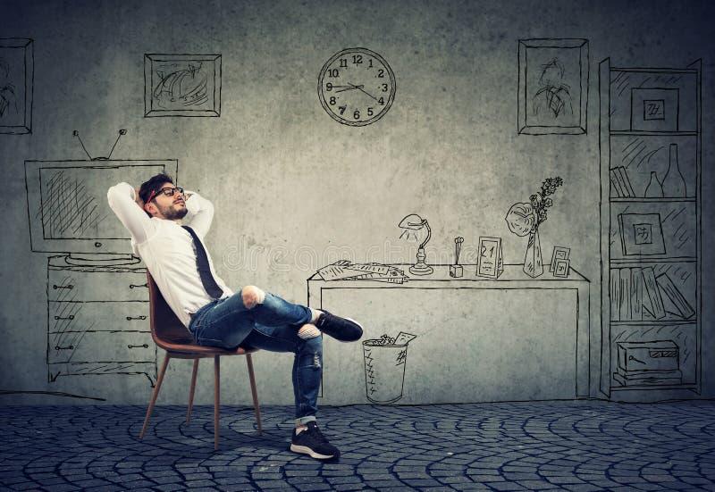 Hombre relajado del inconformista del entreprenur que se sienta en su oficina imagen de archivo libre de regalías