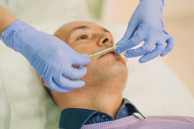 Hombre relajado que tiene un masaje de cara y un tratamiento de la peladura fotos de archivo
