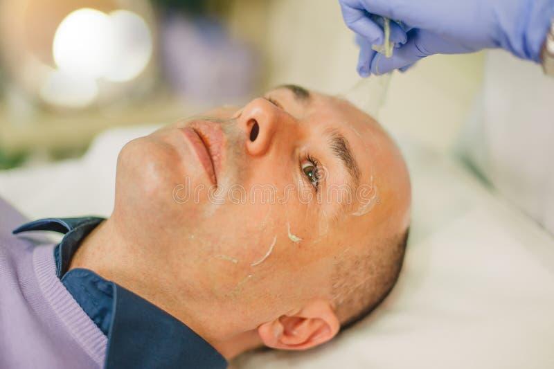 Hombre relajado que tiene un masaje de cara y un tratamiento de la peladura imagenes de archivo