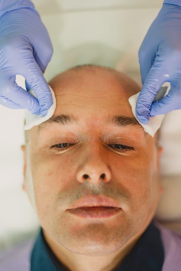 Hombre relajado que tiene un masaje de cara y un tratamiento de la peladura imagen de archivo