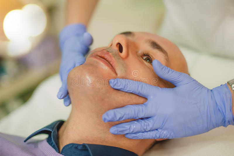 Hombre relajado que tiene un masaje de cara y un tratamiento de la peladura imágenes de archivo libres de regalías