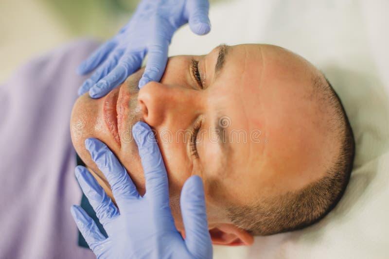 Hombre relajado que tiene un masaje de cara y un tratamiento de la peladura fotografía de archivo