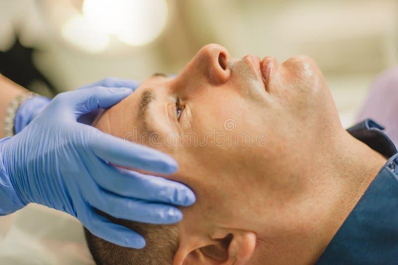 Hombre relajado que tiene un masaje de cara y un tratamiento de la peladura imagen de archivo libre de regalías