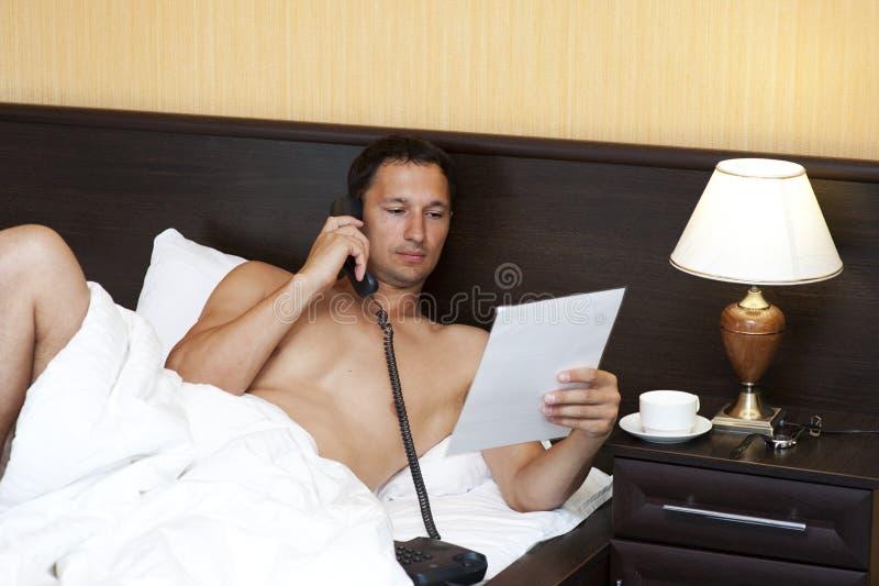 Hombre Relaxed en cama que llama por el teléfono imagen de archivo