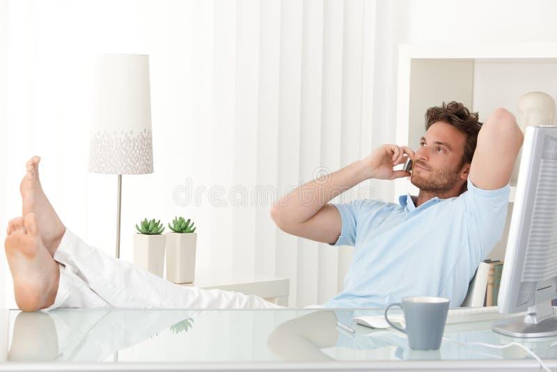 Hombre Relaxed que habla en el teléfono móvil en el escritorio fotos de archivo