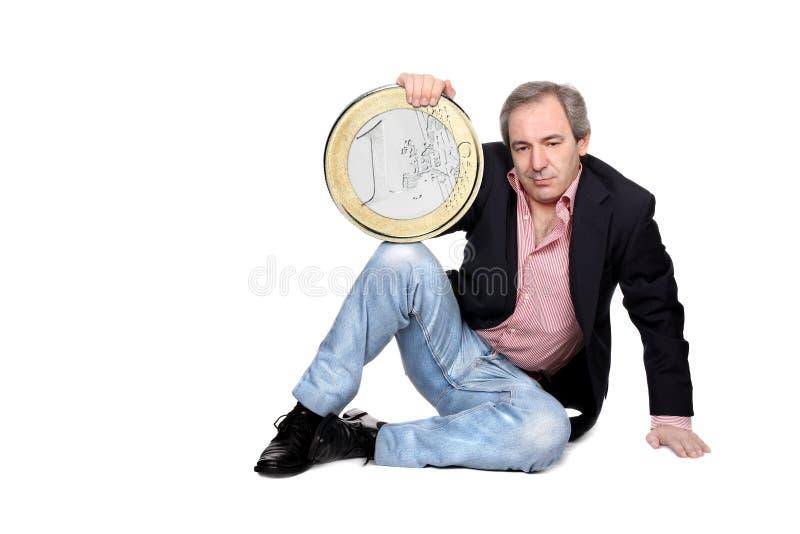 Hombre Relaxed que sostiene una moneda euro fotografía de archivo