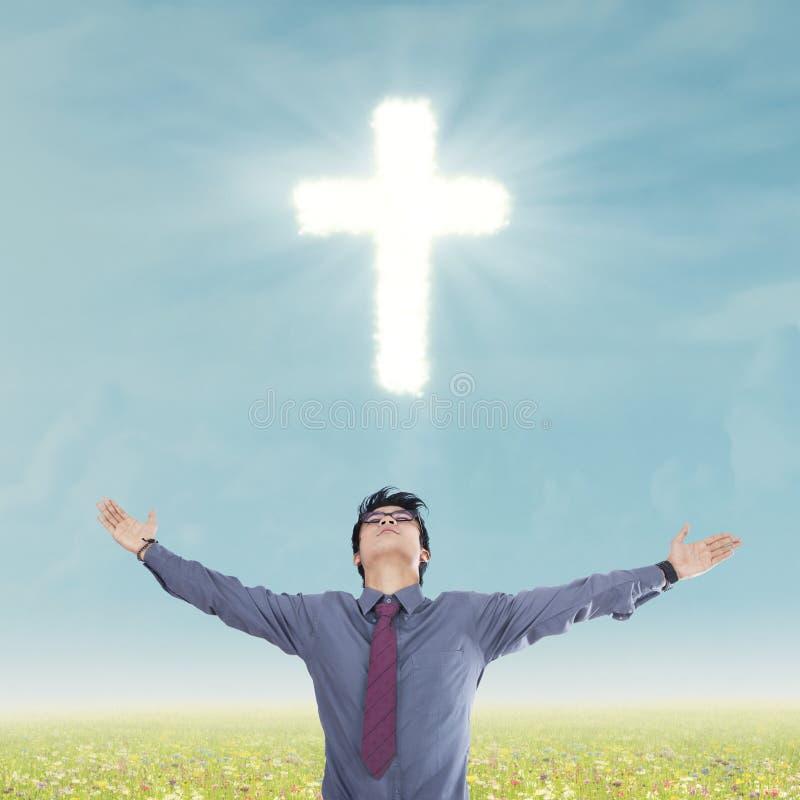Hombre religioso debajo de la cruz imagen de archivo libre de regalías
