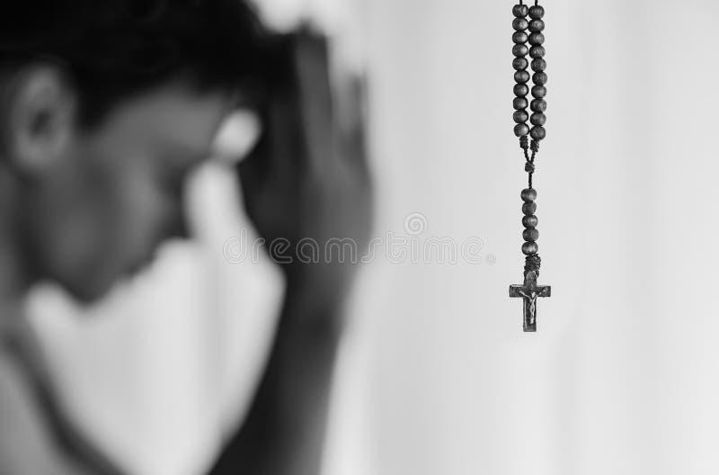 Hombre religioso en rezo con su neckalace cruzado del rosario, en el hime fotos de archivo libres de regalías