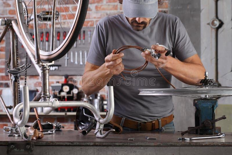 Hombre repare la bicicleta vintage en el taller de taller de taller de taller de taller con herramientas, concepto diy imagen de archivo