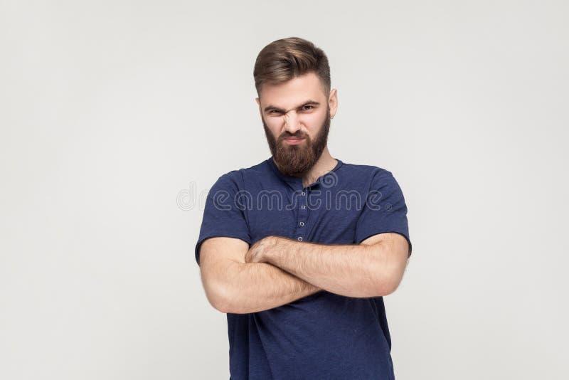 Hombre resentido, con los brazos doblados, sobre fondo gris fotos de archivo libres de regalías
