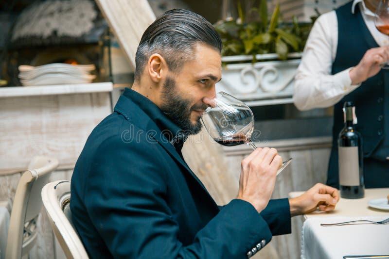 Hombre rico barbudo hermoso con el bigote elegante y barba que sostiene el vidrio y el olor de la aspiración del vino rojo en el  imagen de archivo