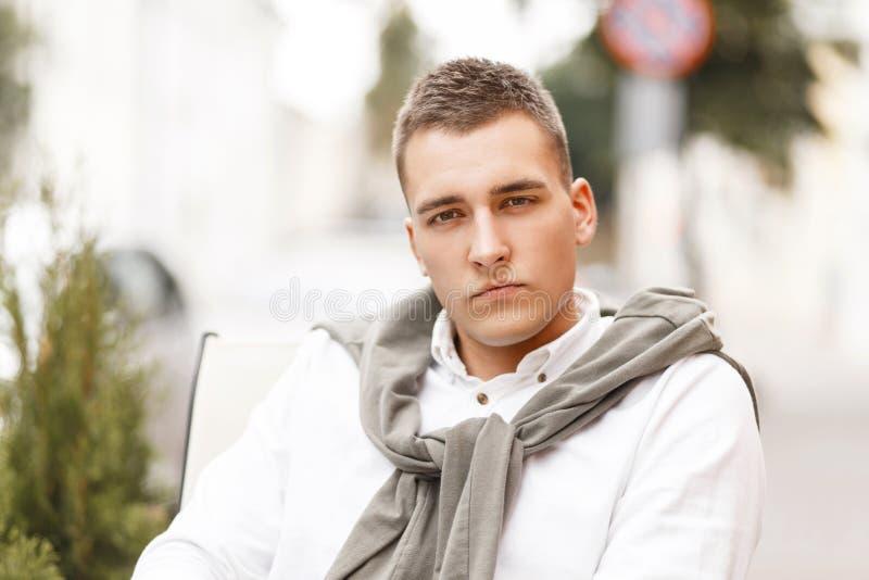Hombre rico elegante hermoso en una camisa blanca con un suéter foto de archivo