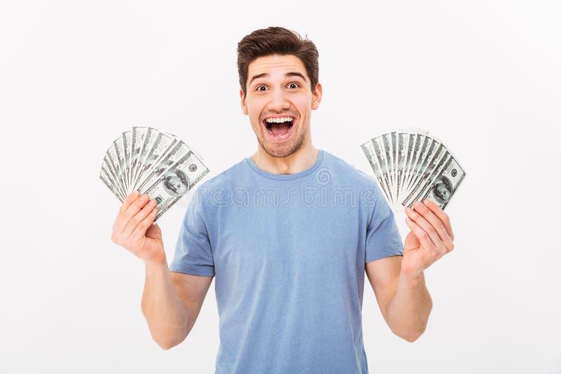 Hombre rico joven en la camiseta casual que sostiene dos fans de dolla del dinero imagen de archivo