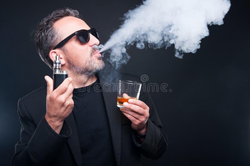 Hombre rico que exhala el vapor de un cigarrillo electrónico imágenes de archivo libres de regalías
