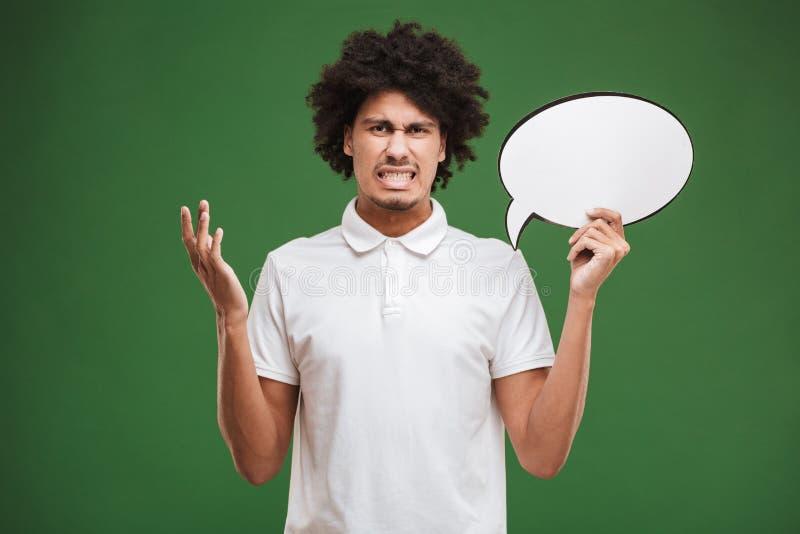Hombre rizado africano joven confuso que lleva a cabo la burbuja del discurso fotos de archivo libres de regalías