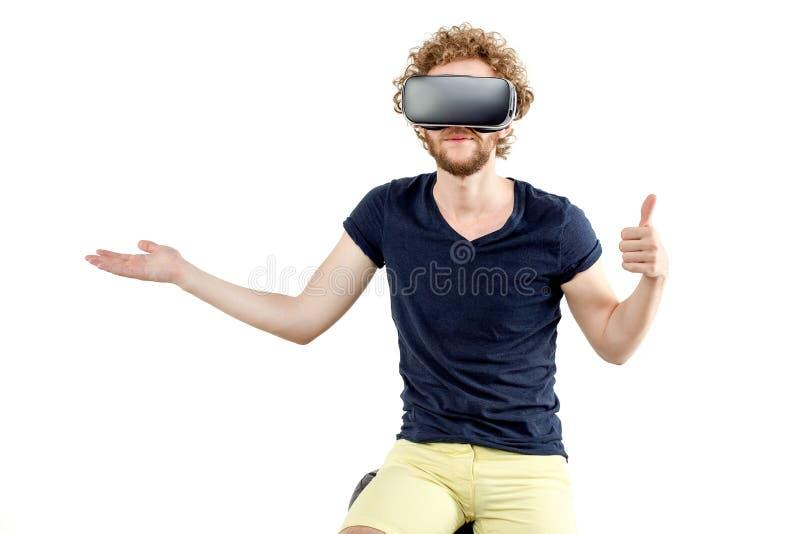 Hombre rizado-cabelludo joven que usa auriculares de VR y experimentando virtu imagenes de archivo