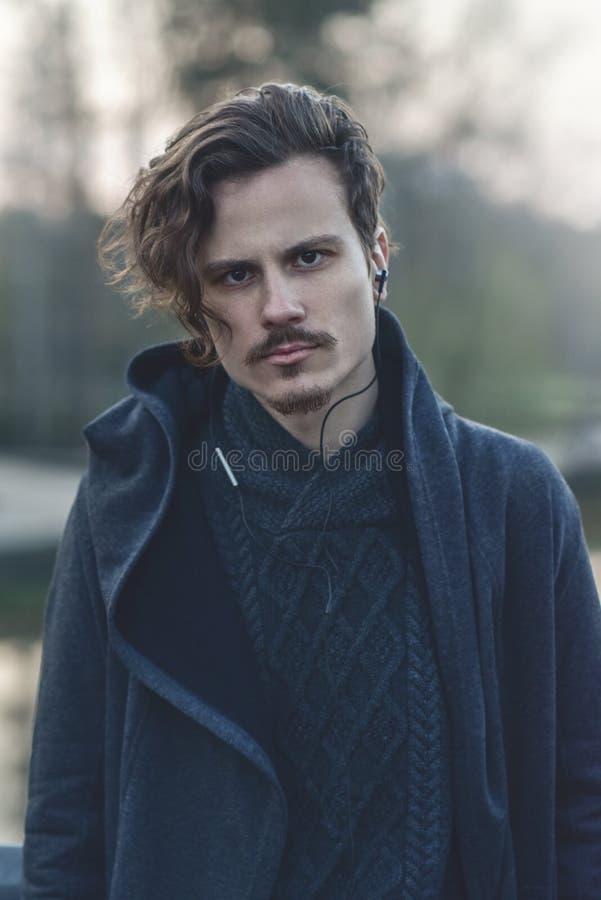 Hombre rizado joven brutal hermoso con un corte de pelo elegante que escucha la m?sica imagen de archivo libre de regalías