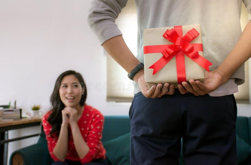 Hombre romántico hermoso que oculta una caja de regalo detrás de su asombrosamente trasero su novia en día especial foto de archivo