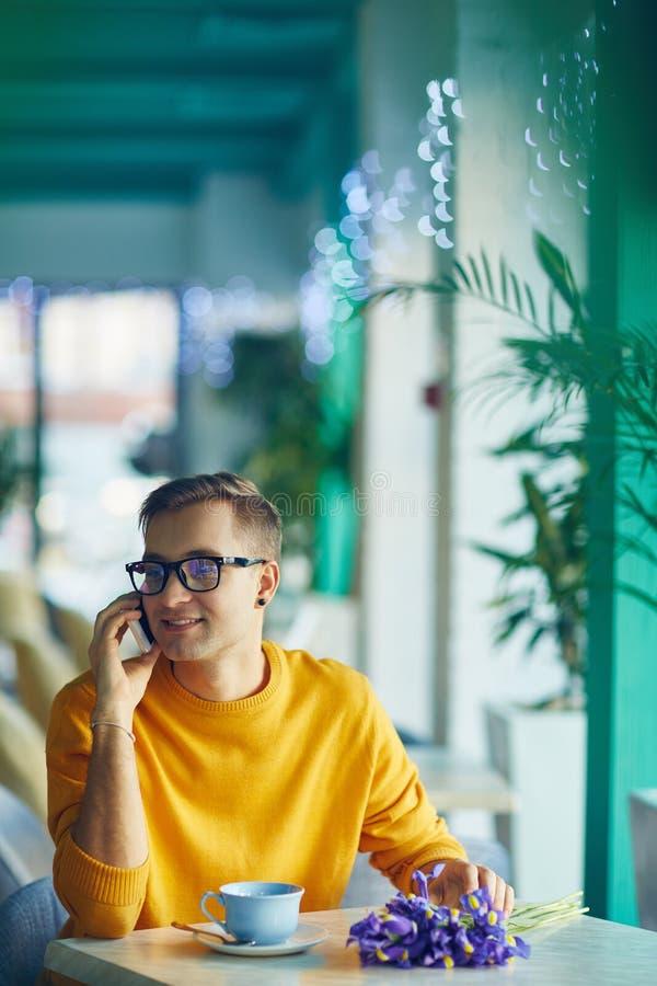 Hombre romántico que habla por el teléfono en café fotografía de archivo
